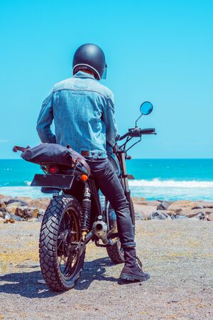 A person sitting on the motorcycle while looking at the ocean Stock Photo
