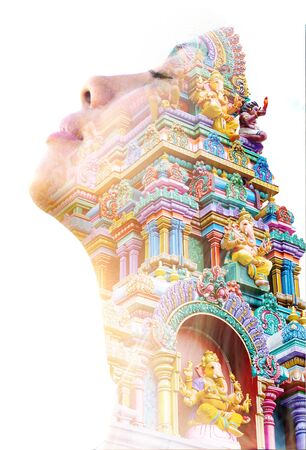 Double exposure portrait of a young female traveller with closed eyes and tilting her head back combined with colorful hindu statue from a temple 版權商用圖片