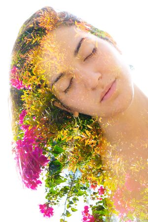 Double exposure close up portrait of a young pretty woman interwoven with bright leaves of a vibrant tropical tree with exotic pink flowers seemingly growing from her hair