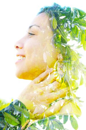 Double exposure profile portrait of a young, relaxed natural beauty large golden earrings and long brown hair combined with green tropical leaves on a white background