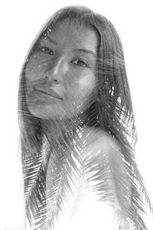 Double exposure portrait of a young ethnic beauty combined with tree leaves, black and white