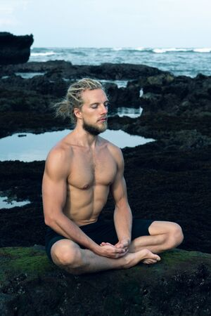 Athlete man practicing yoga outdoors photograph Фото со стока - 147097305