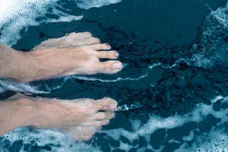 Male feet on black sand beach shore