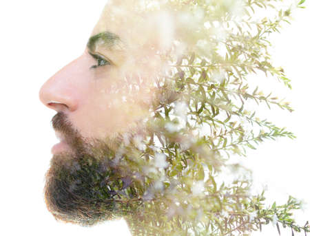 A bearded bold man profile double exposure portrait close up combined with a photo dark green tree branches