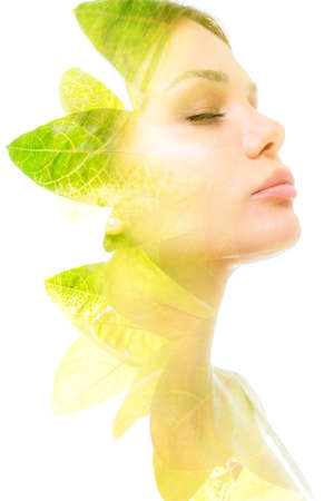 A double exposure portrait of a womans profile with her eyes closed combined with a photo of green leaves of a plant