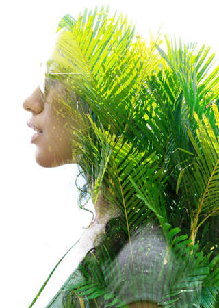 A double exposure portrait of a young woman profile with sun glasses against white background with palm tree leaves