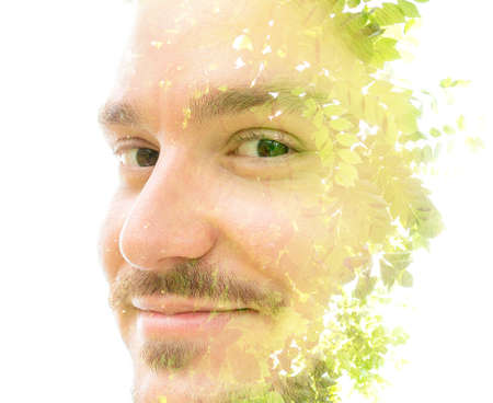 A smiling mans double exposure portrait close up with green leaves