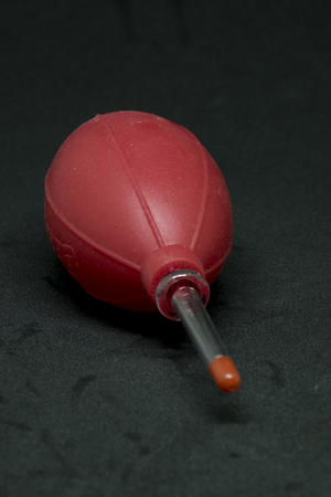 air cleaner: Mano que sostiene el fuelle de goma o de la bomba del ventilador de polvo limpiador de lentes de cámara y en el fondo