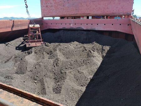 Opération de déchargement de charbon sur navire en vrac.