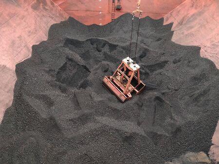 Coal discharging operation by crane's grab on bulk ship.