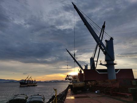 Discharging or loading operation on bulk ship in morning.
