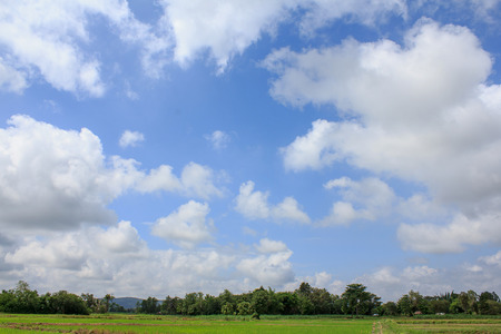 distinctness: Beautiful white clouds,Bright blue sky and there are mountains and green fields below. Stock Photo