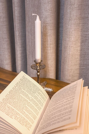 Candle with books on the wooden desk and background photo