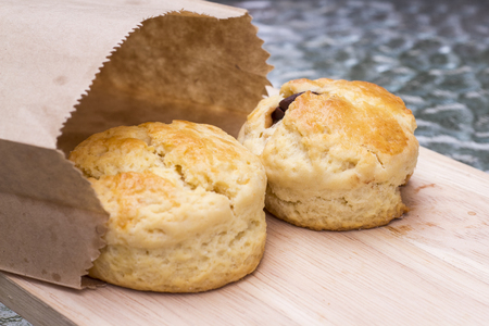 scone: Scone on wooden plate and paper bag.