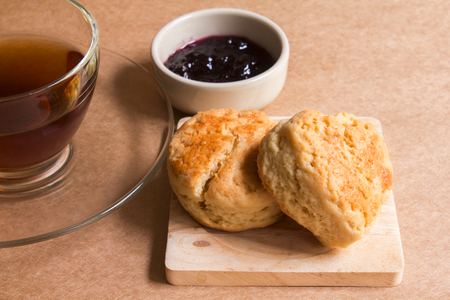 scone: Scone with hot tea and blueberry jam.