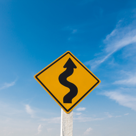 Yello traffic sign in front of a deep blue sky.