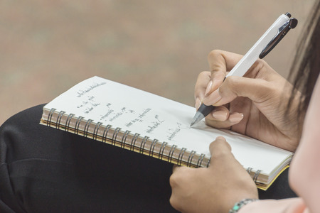soft focus of somone is writing on  a notepad in vintage color