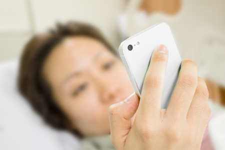 a patient is using smart phone in bed