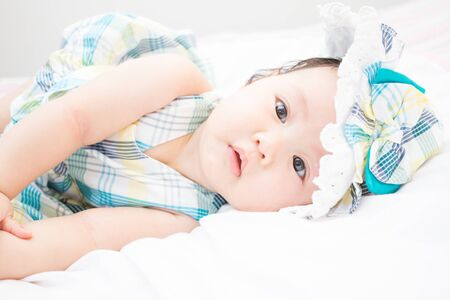 a beautiful baby is looking in something. this picture include copy space