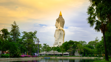devote: White giant Buddha statue in Thailand background sky sunset