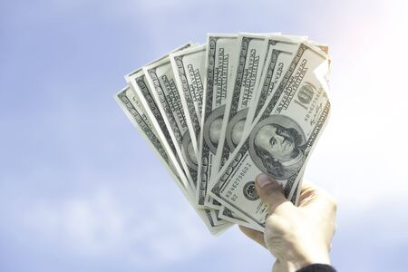inducement: hand holding US dollar against blue sky
