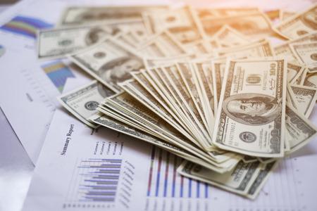 cuadro sinoptico: Gráfica, texto del informe resumen y dinero en el fondo de color abstracta mesa