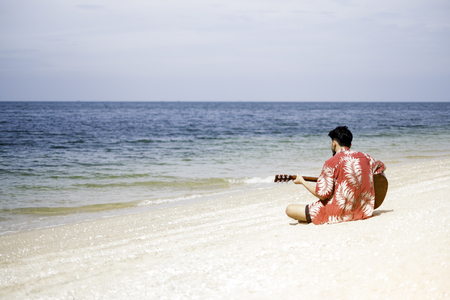 Handsome young man playing guitar on the beach
