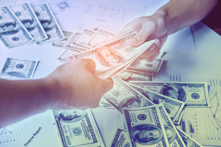Close-up Of Person Hand Giving Money To Other Hand background United States dollar (USD) bills on table Stock Photo