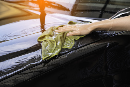 valeting: hand women hold water over the car for washing with microfiber cloth Stock Photo
