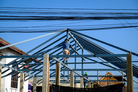 worker installing structure of roof steel for new building at construction site, thailand local home
