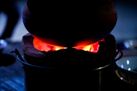 wood burner: clay pot on fireplace, Stove Burner Charcoal at night, Thailand local Stock Photo