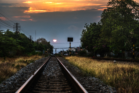 Railroad against beautiful sky at sunset. Industrial landscape with railway station, colorful blue sky, trees and grass, yellow sunlight. Railway junction. Heavy industry. Railways. Stock Photo