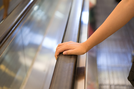 second floor: Point of view of a women riding an escalator to the second floor of the mall. One hand visible in the frame holding the escalator rail. Stock Photo