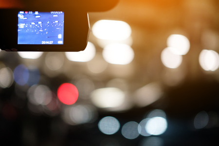 A camera in car has on and recording at the car park with bokeh background in the night. Stock Photo