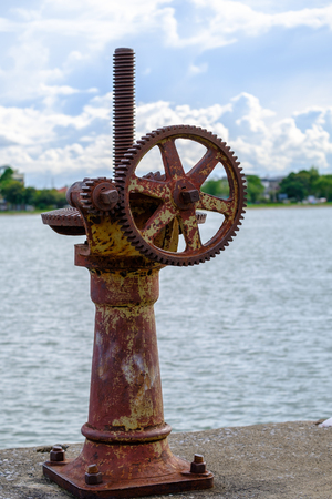 Old gear and rusted cogwheel mechanism, cog gear wheel for watergate on nature background.