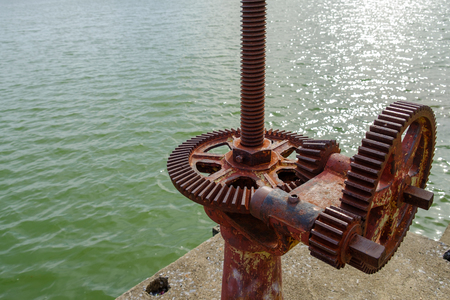 Old gear and rusted cogwheel mechanism, cog gear wheel for watergate on nature background, Watergate at a canal in the countryside keeps water in the rainy season.To use in agriculture local thailand