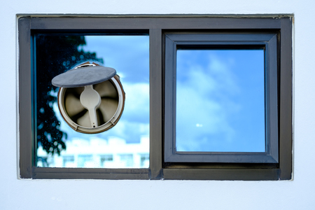 Window on modern home, Ventilators on dirty glass window, Dusty exhaust fan mounted in a glass window closeup 免版税图像