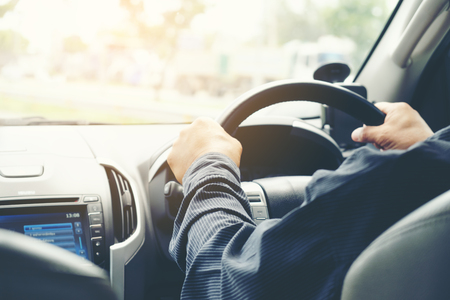 Car driver hands holding steering wheel.