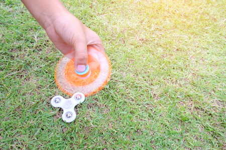 Boy holding play two fidget spinners, Fidget spinner white and ogange colour spinning stress relieving toy on green grass background.