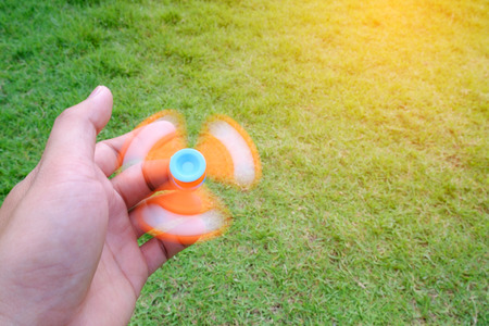 Boy holding play fidget spinners, Fidget spinner ogange colour spinning stress relieving toy on green grass background.