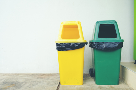 Yellow and Green plastic trash Recycle Bin on the floor and white wall