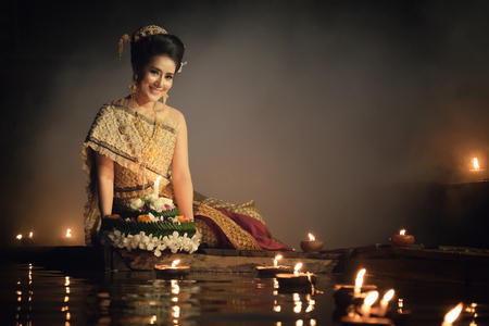Loy Krathong Traditional Festival, Thai woman hold kratong, Thailand, Asia woman in Thai dress traditional hold kratong and bring Krathong to float in Loi kratong day of Thailand. Banco de Imagens