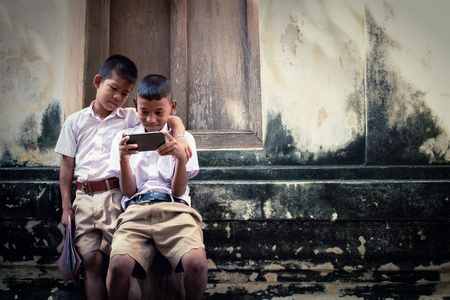Two asian boys wearing school uniforms are playing game but they are not reading book, old wall temple background Local Thailand 写真素材