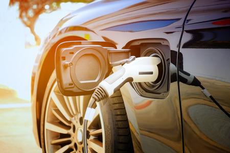 Aufladen der modernen Batterie des Elektroautos auf der Straße, die die Zukunft des Automobils sind, Nahaufnahme der Stromversorgung in einem Elektroauto, das für Hybrid aufgeladen wird Neue Ära des Kraftstoffs für Fahrzeuge. Standard-Bild