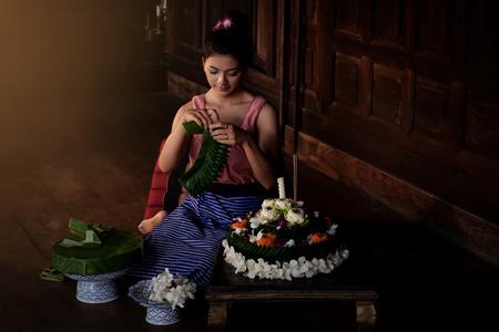 전통적인 드레스를 입고 태국의 아름다운 여성은 태국 치앙마이의 ningt에서 Loi Krathong 축하 축제 기간 동안 Krathong 꽃 그릇에 바나나 잎을 만듭니다.