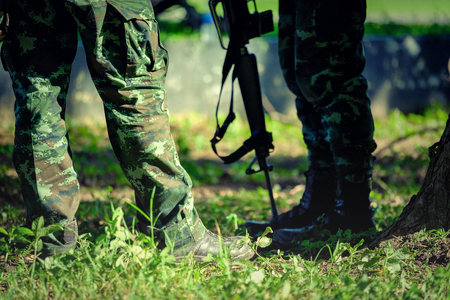 troop: Thai Soldiers with military camouflage uniform in army formation (military, army). soldier wearing camouflage uniform with gun - closeup on his leg and boot in forest