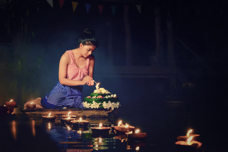 Loy Krathong Traditional Festival, Thai woman dress traditional sitting hold kratong and light the candle in Thailand. Stock Photo