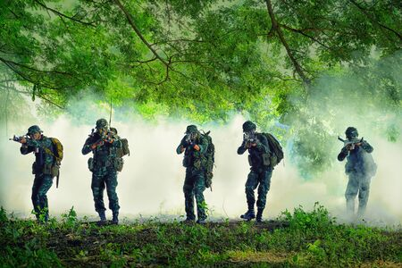 Military Thailand: Lopburi, THAILAND - Oct 22, 2017 - Thai soldier holding gun in full army uniform. Rangers to find news, kneeling and looking at the enemy, the battle in the mountain forests.Tactical military training ground