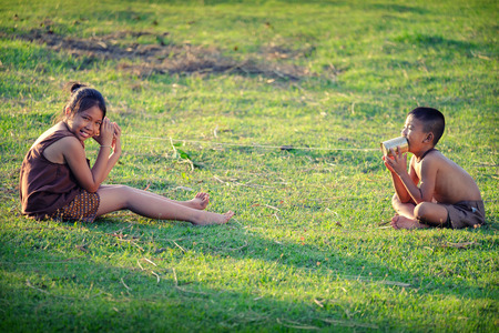 농촌 어린이들은 전화로 의사 소통을합니다. 농촌 아시아 어린이들의 의사 소통의 즐거움.