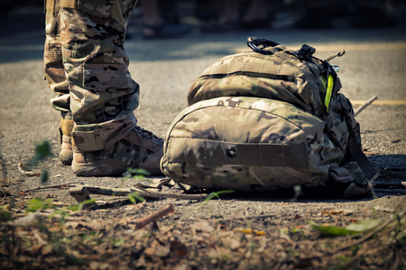 Soldiers stand with bag. Army, Military Boots lines of commando soldiers in camouflage uniforms